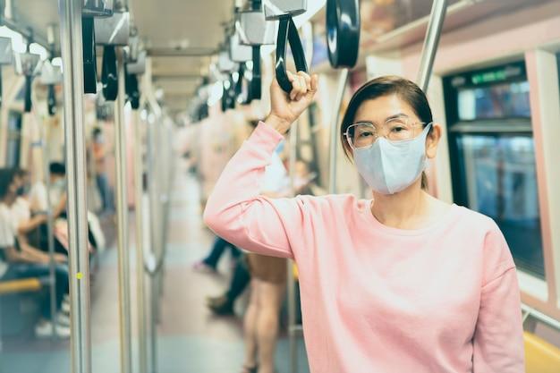 Aziatische vrouw die beschermingsmasker draagt dat zich in ondergrondse trein bevindt