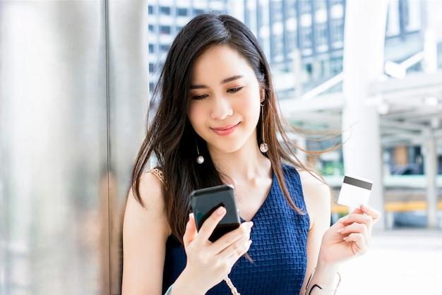 Aziatische vrouw die betaling met creditcard verricht die mobiele telefoontoepassing gebruikt