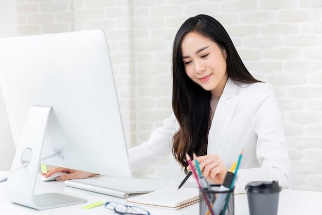 Aziatische vrouw die bij haar bureau in het bureau werkt
