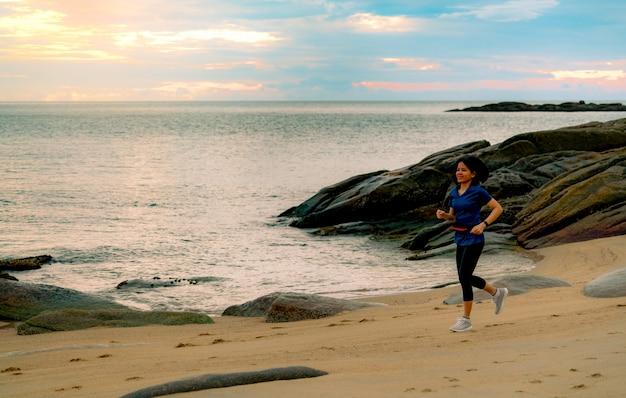 Aziatische vrouw die bij tropisch overzees strand in de ochtend met mooie zonsopganghemel loopt. fit gezonde vrouw buiten training. fit meisje draag slimme band en heuptas. vrouw loopt.