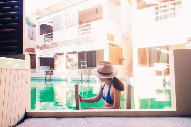 Aziatische vrouw die bikini en strohoed in zwembad draagt. reizen vakantie concept