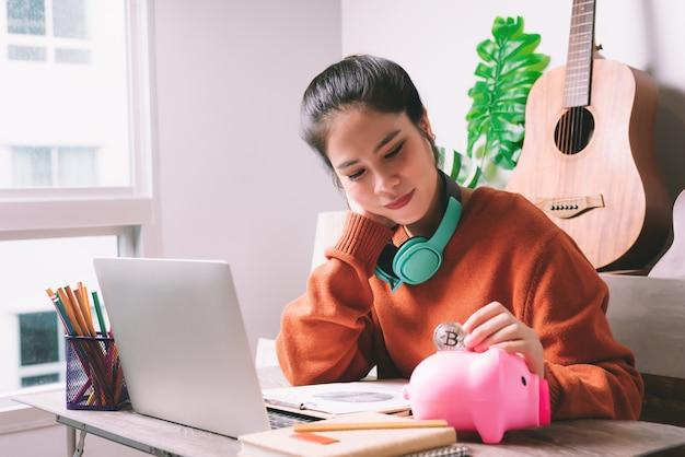 Aziatische vrouw die bitcoin-muntstuk zetten in roze spaarvarken voor het besparen van het beheer van de geldrijkdom - financiën of besparingenconcept