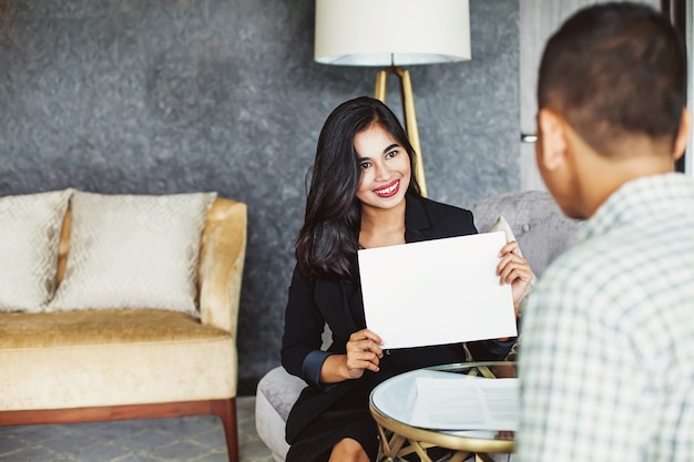 Aziatische vrouw die blanco papier toont aan een klant