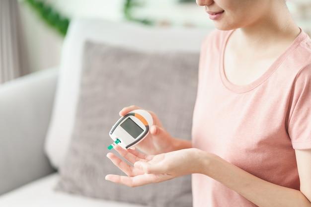 Aziatische vrouw die bloedsuikerspiegel controleert door digitale glucosemeter, gezondheidszorg en medisch, diabetes, glycemieconcept