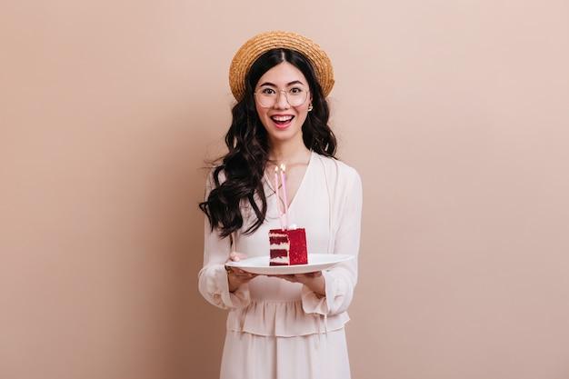 Aziatische vrouw die camera met glimlach bekijkt. gelukkige japanse vrouw in de cake van de strohoedholding.