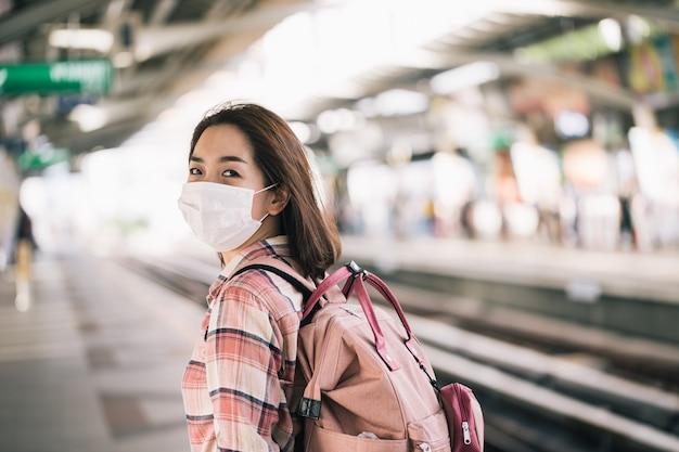 Aziatische vrouw die chirurgisch gezichtsmasker draagt tegen nieuwe coronavirus of coronavirusziekte bij openbaar treinstation