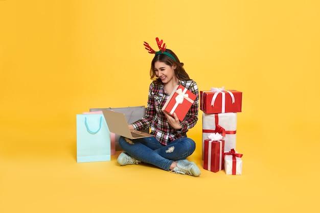 Aziatische vrouw die computer met behulp van om online giftdoos te winkelen geïsoleerd op gele achtergrond. cyber maandag en kerstmis nieuwjaar concept.