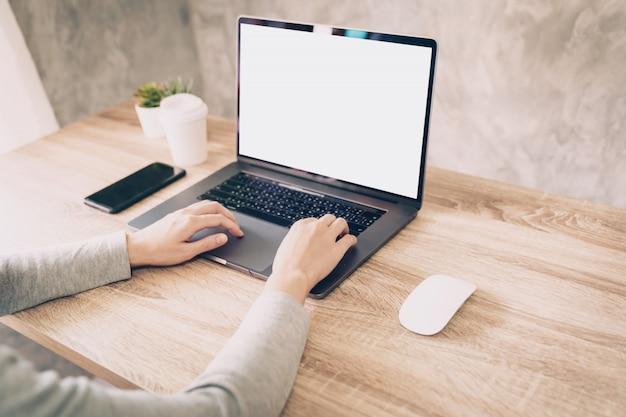 Aziatische vrouw die computerlaptop voor het werken aan houten lijst met behulp van