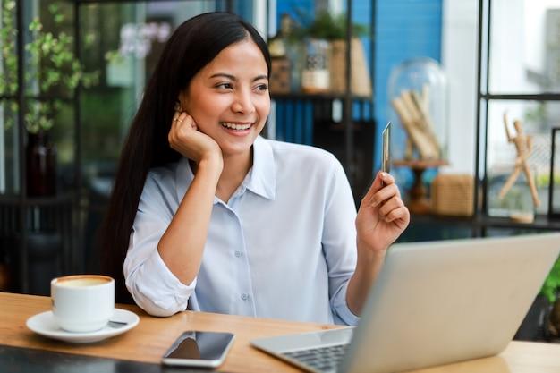 Aziatische vrouw die creditcard gebruikt die online in de koffie van de koffiewinkel winkelt