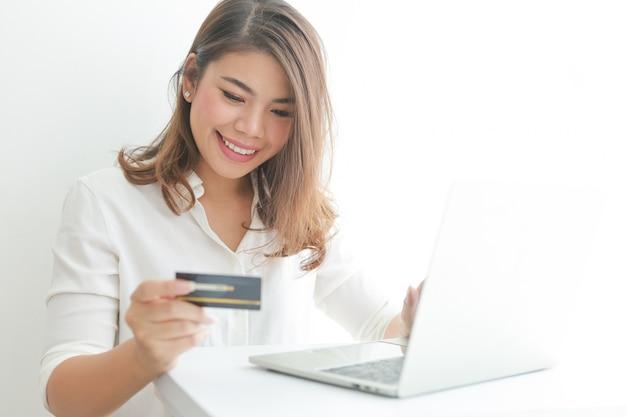 Aziatische vrouw die creditcard gebruikt die online met laptop computer winkelt,