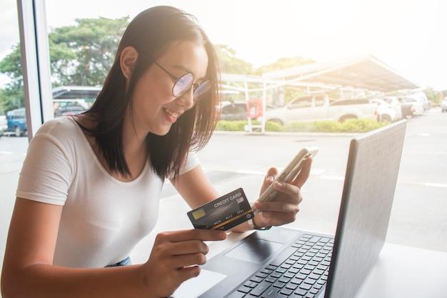 Aziatische vrouw die creditcard gebruikt die online winkelt