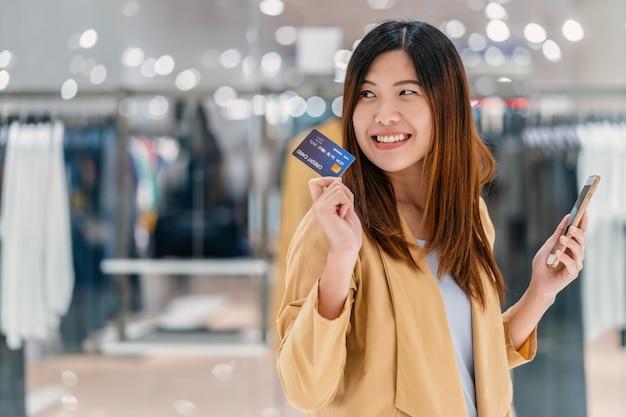 Aziatische vrouw die creditcard met mobiele telefoon voor online het winkelen in warenhuis met behulp van