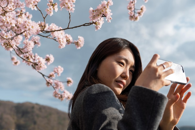Aziatische vrouw die de aard waardeert die haar omringt