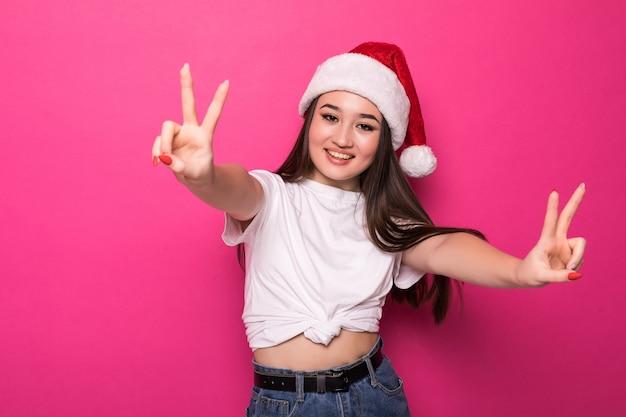 Aziatische vrouw die de hoed van de kerstman met vredesgebaar draagt dat op roze muur wordt geïsoleerd