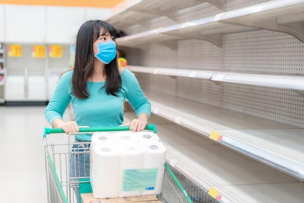 Aziatische vrouw die de lege toiletpapierplanken van de supermarkt temidden van covid-19 coronavirusangsten bekijkt, shoppers in paniek kopen en toiletpapier opslaan dat zich voorbereidt op een pandemie.