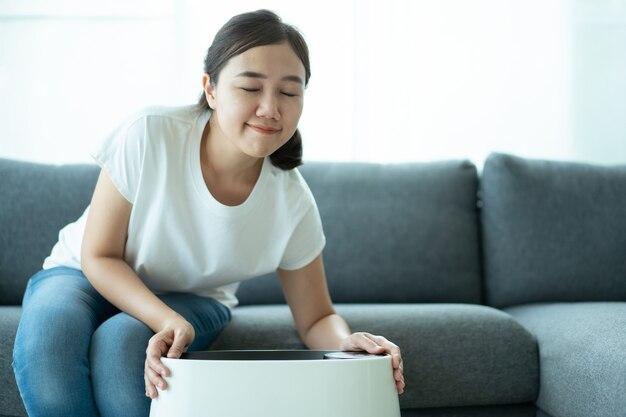 Aziatische vrouw die de moderne luchtreiniger aanzet en gebruikt terwijl ze in de woonkamer verblijft, luchtreiniger is een populair apparaat - huishoudelijke elektriciteit. luchtreiniger kan helpen om de lucht te zuiveren.