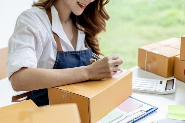 Aziatische vrouw die de verzendinformatie van de klant op de pakketdoos schrijft, ze is eigenaar van een online winkel, ze verzendt producten naar klanten via een particulier koeriersbedrijf. online verkoopconcept.