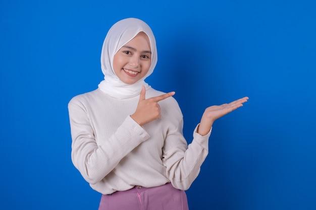 Aziatische vrouw die de witte uitdrukking van de t-shirtglimlach met haar hand gebruikt
