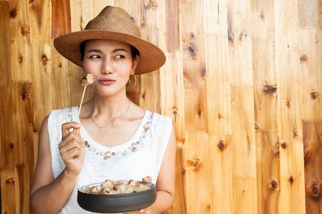 Aziatische vrouw die dessert eet dat van banaan wordt gemaakt