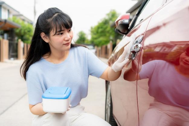 Aziatische vrouw die deurklink van rode auto desinfecteert door desinfecterende wegwerpdoekjes uit doos. voorkom het virus en de bacteriën, voorkom covid19, coronavirus
