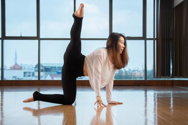 Aziatische vrouw die dichtbij venster danst