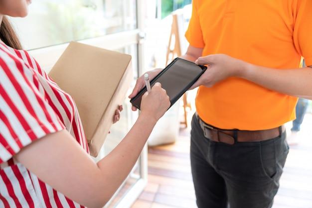 Aziatische vrouw die digitaal teken schrijven die pakketdoos op tablet ontvangen van de leveringsman in oranje eenvormig bij haar thuis. de leveringsdienst.