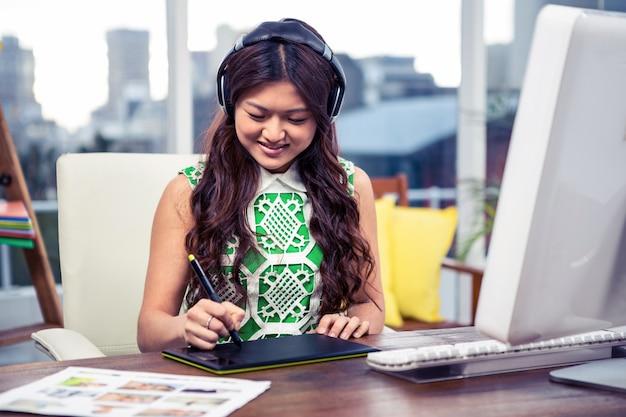 Aziatische vrouw die digitale raad in bureau gebruikt