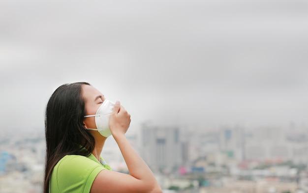 Aziatische vrouw die door een beschermingsmasker tegen luchtvervuiling in de stad van bangkok ademt te dragen