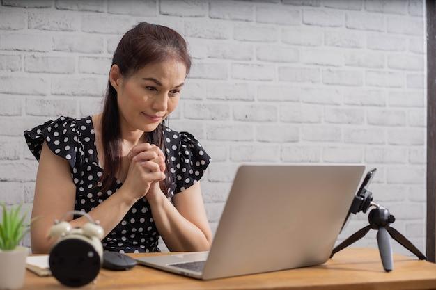 Aziatische vrouw die door geloof bidt met computerlaptop, online concept van kerkdiensten