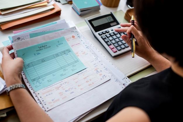 Aziatische vrouw die door papierwerk werkt