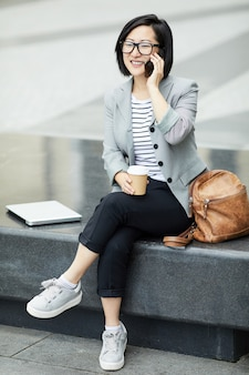Aziatische vrouw die door smartphone in openlucht spreken