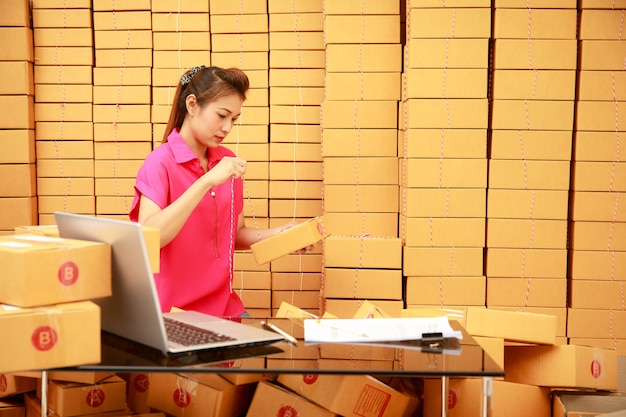 Aziatische vrouw die dozen inpakt in haar online winkelzaken thuis