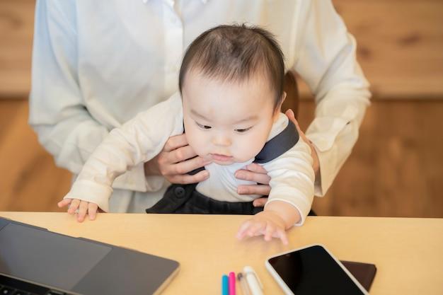 Aziatische vrouw die een baby houdt en laptop binnen in werking stelt