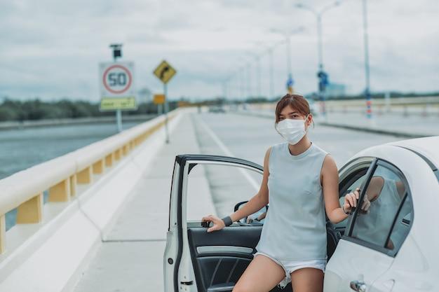 Aziatische vrouw die een beschermend gezichtsmasker draagt, beschermt de veiligheid voordat ze uit de auto stapt tijdens een pandemie van de coronavirus covid-19 avondklok buiten