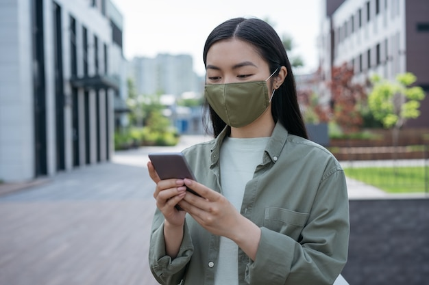 Aziatische vrouw die een beschermend gezichtsmasker draagt dat online mobiele telefooncommunicatie gebruikt