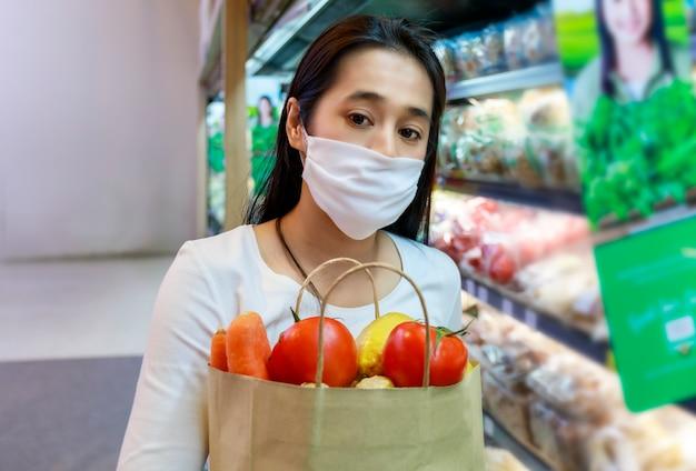 Aziatische vrouw die een beschermend gezichtsmasker draagt, houdt papieren boodschappentas met groenten en fruit in de supermarkt.