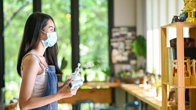 Aziatische vrouw die een beschermend masker draagt met alcohol-antiseptische gel voorkomt uitbraak van covid-19 in café