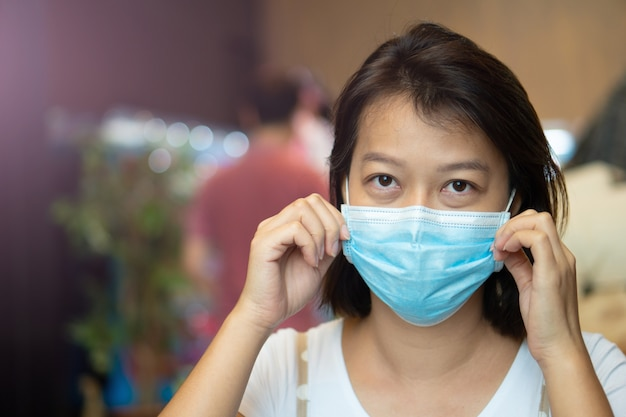 Aziatische vrouw die een beschermend masker op haar gezicht draagt terwijl ze in de coffeeshop is tijdens de pandemie van het virus covid-19.