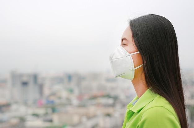 Aziatische vrouw die een beschermingsmasker draagt tegen pm 2.5 luchtvervuiling in de stad van bangkok. thailand.
