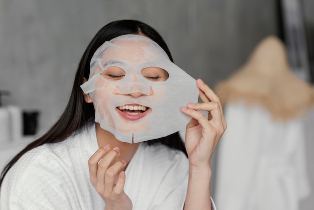 Aziatische vrouw die een bladmasker gebruikt
