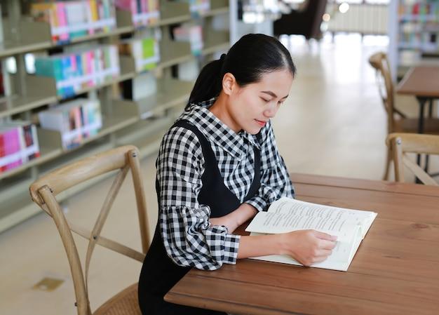Aziatische vrouw die een boek in de bibliotheek leest.