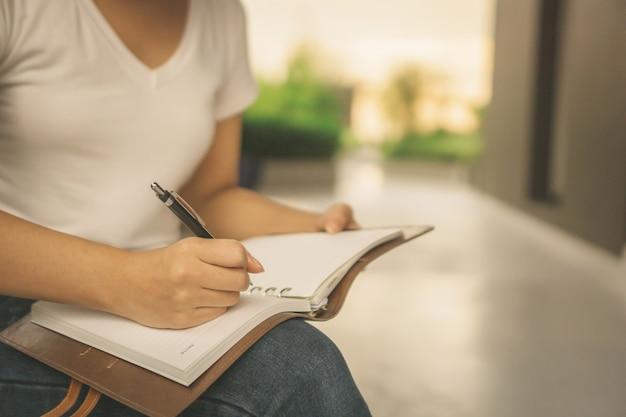 Aziatische vrouw die een boek in park met wolkenkrabbers op de achtergrond leest