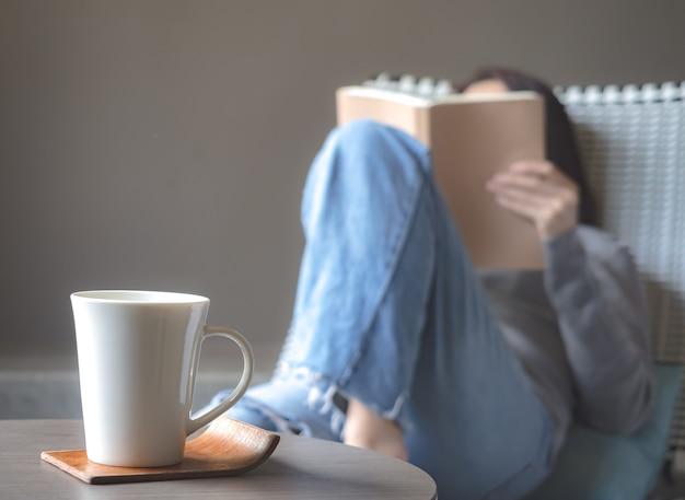 Aziatische vrouw die een boek op de stoel leest