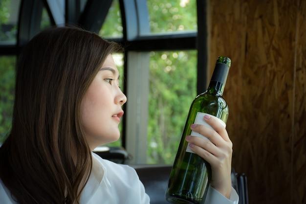 Aziatische vrouw die een fles wijn houdt / vrouw die een fles wijn in restaurant selecteert