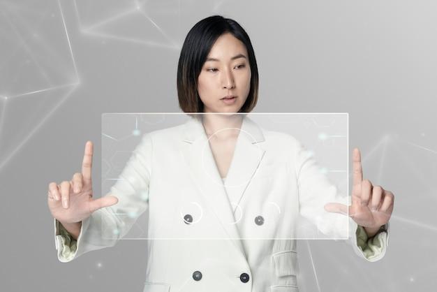 Aziatische vrouw die een futuristische digitale remix met transparant scherm gebruikt