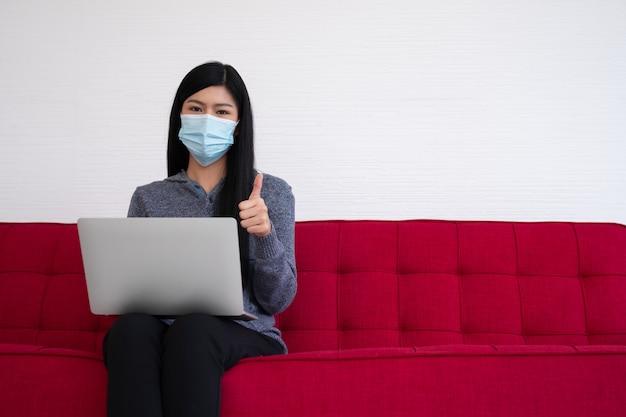 Aziatische vrouw die een gezichtsmasker draagt en laptop op de bank voor het werken van huis en duimen gebruikt.