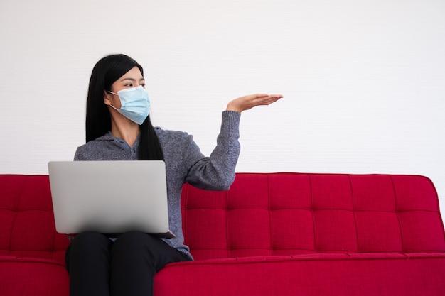 Aziatische vrouw die een gezichtsmasker draagt en laptop op de bank voor het werken vanuit huis gebruikt.