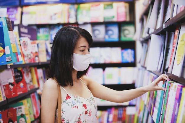 Aziatische vrouw die een gezichtsmasker draagt op een het winkelen plaats