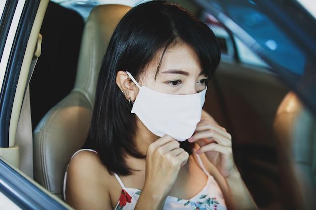 Aziatische vrouw die een gezichtsmasker in auto draagt