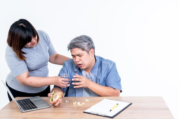 Aziatische vrouw die een glas water overhandigt aan geïsoleerde echtgenoot